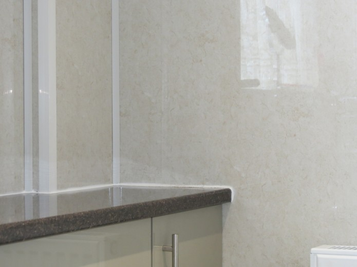 Aquabord wall panels in the corner of a room, with a worktop.